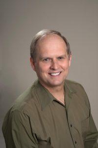 Dr Robin Hanson wearing a green shirt.